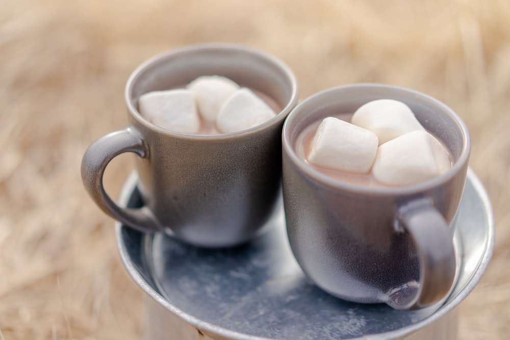 two mugs of beverages and marshmallows