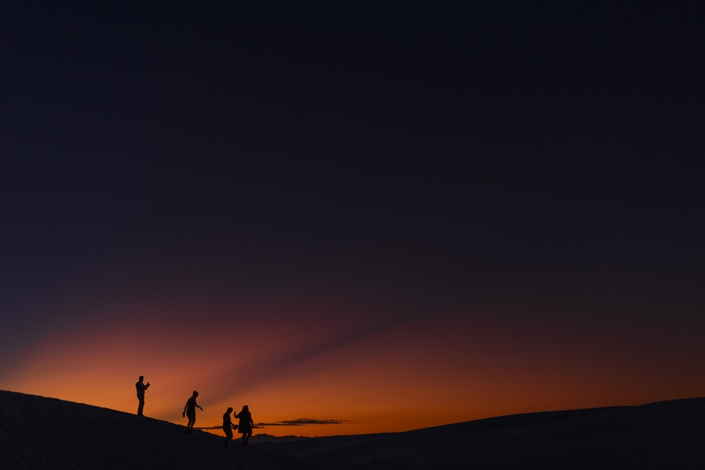 four people standing during golden hour