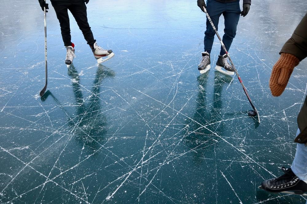 three persons playing ice hockey