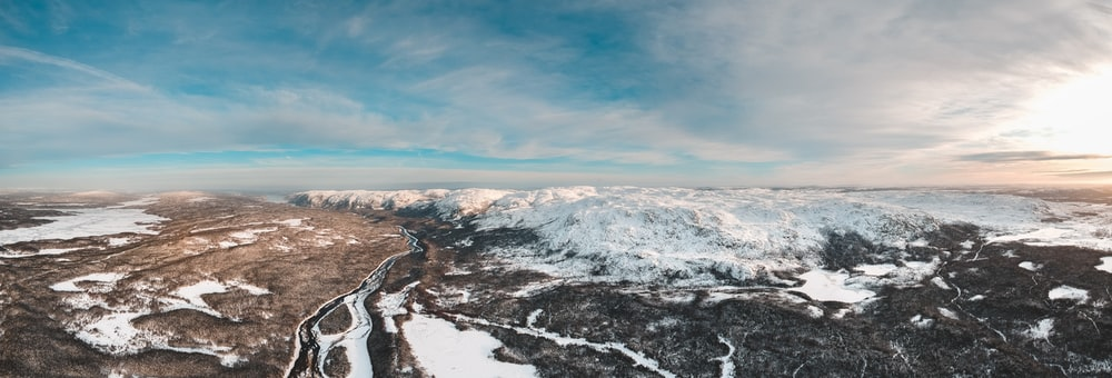 aerial photo of snow covered mountains under cloudy sky