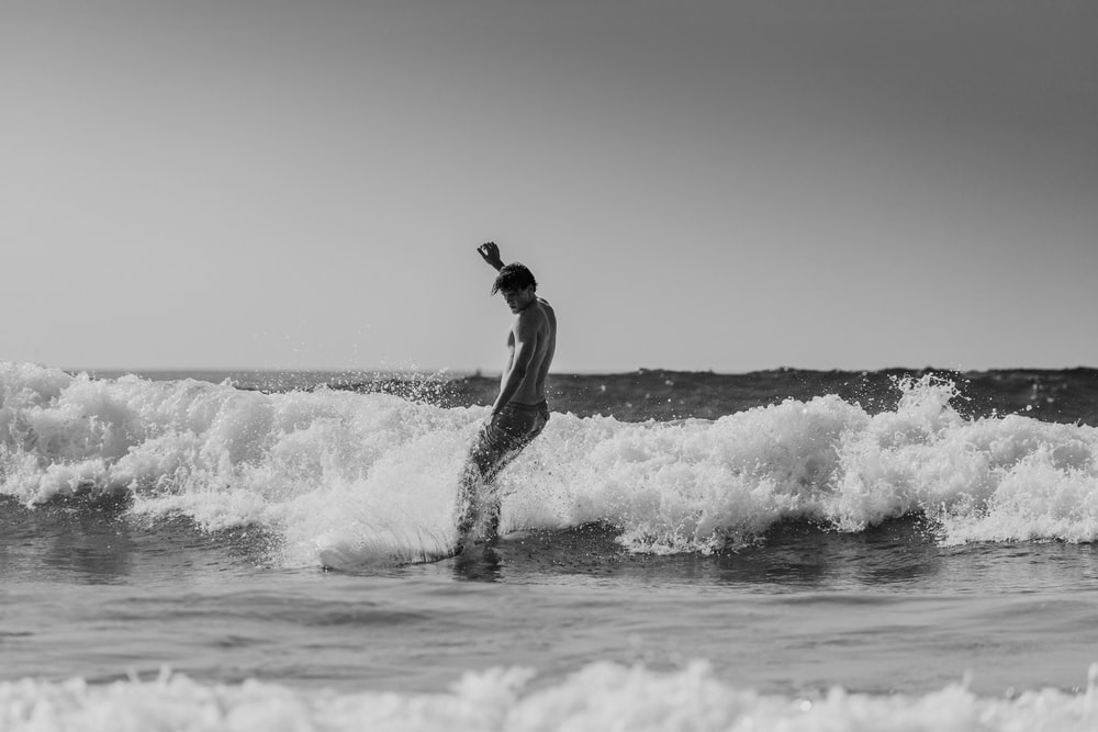 grayscale photography of man surfing in the beach