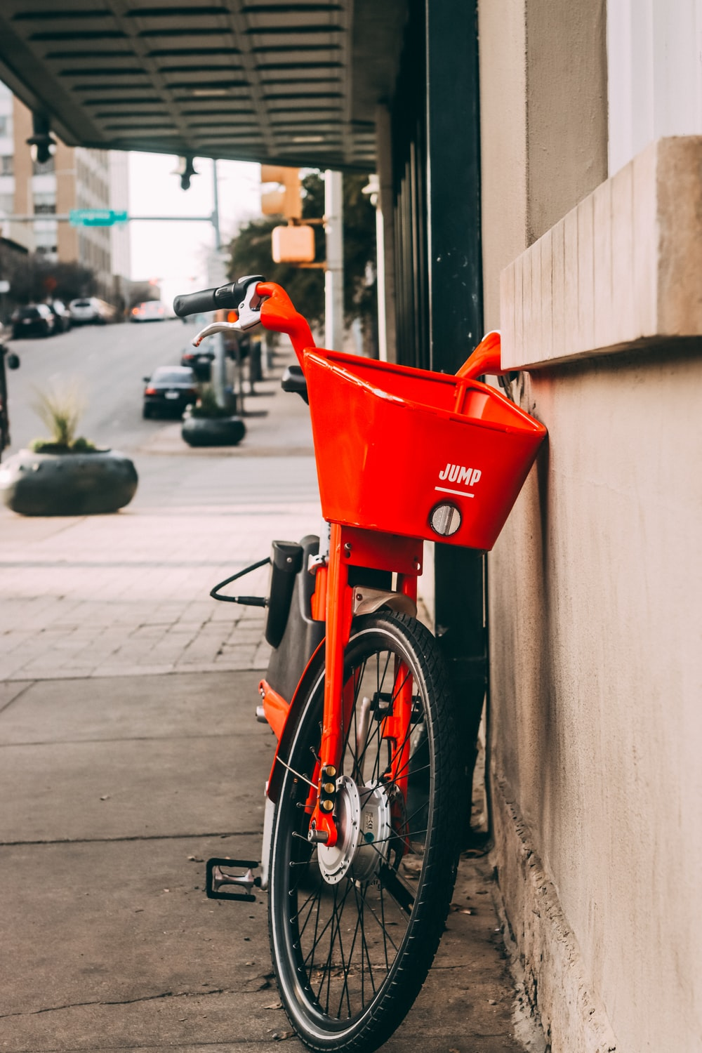 shallow focus photo of red and black bike parked beside sidewalk