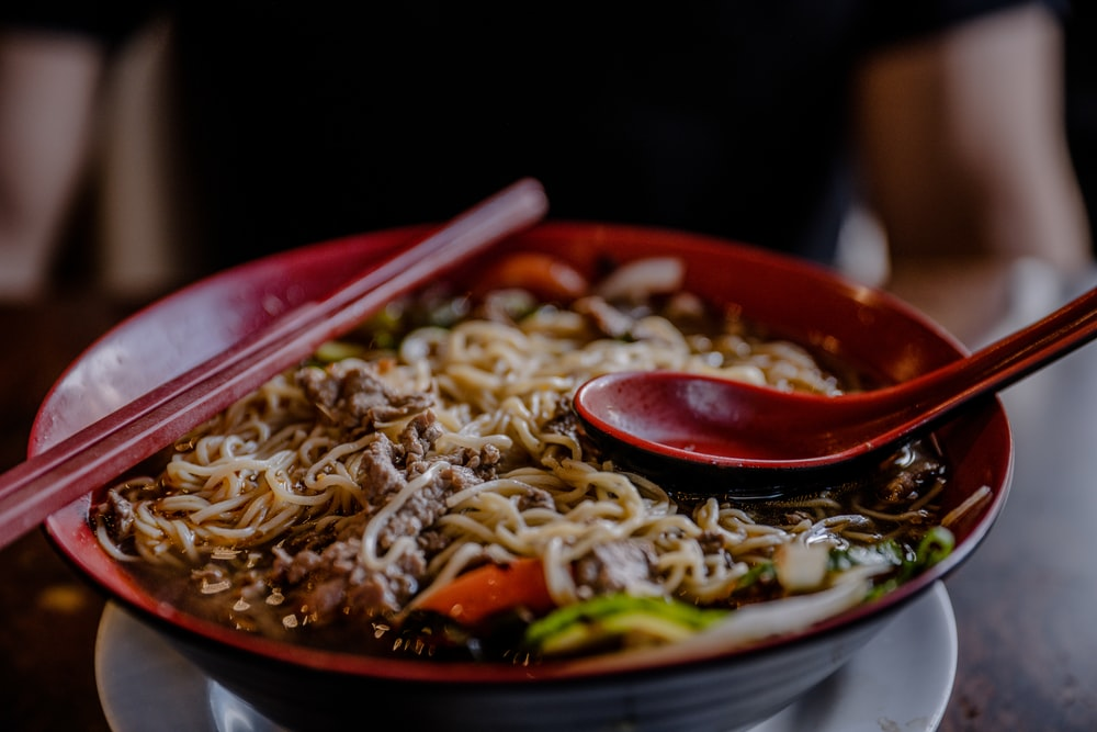noodles with meat in round red bowl