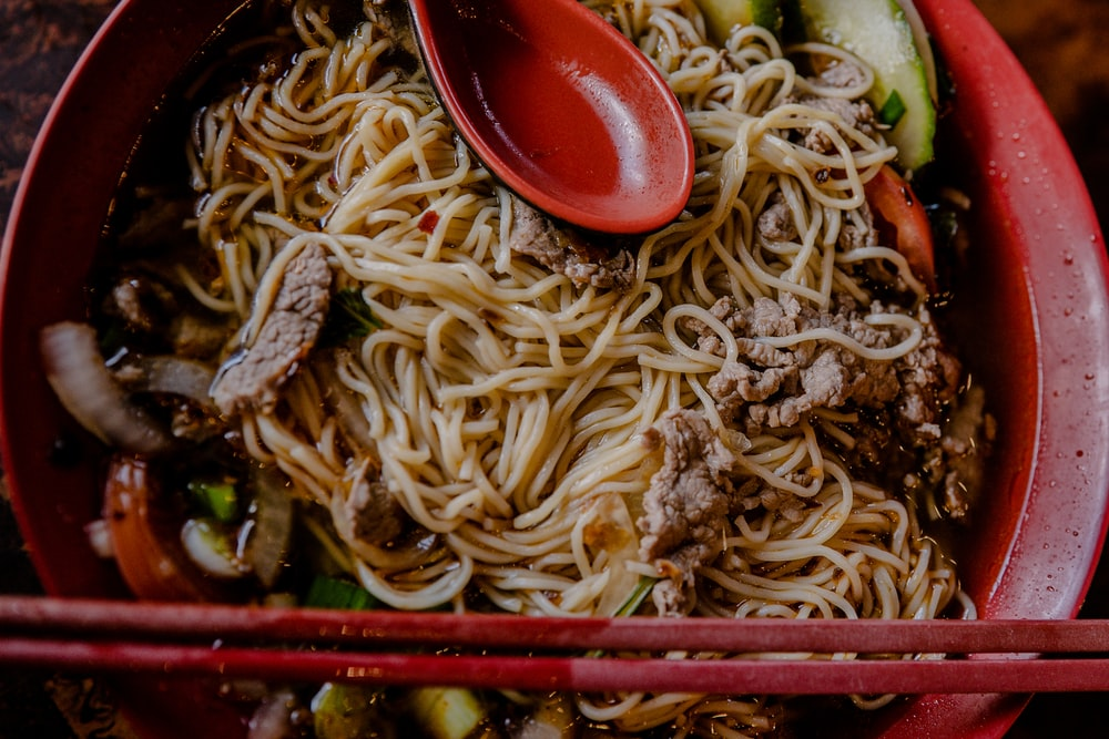 noodles with meat and spring onions in round red bowl