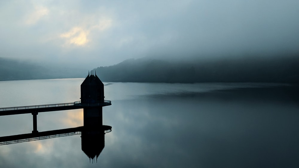silhouette of dock on body of water
