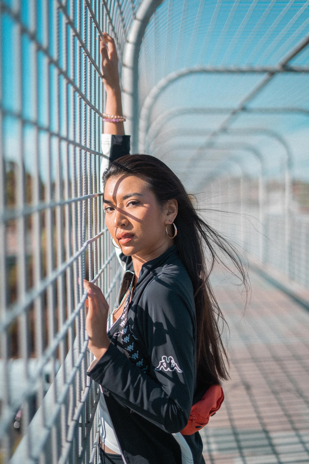 selective focus photography of woman standing in front of chain fence