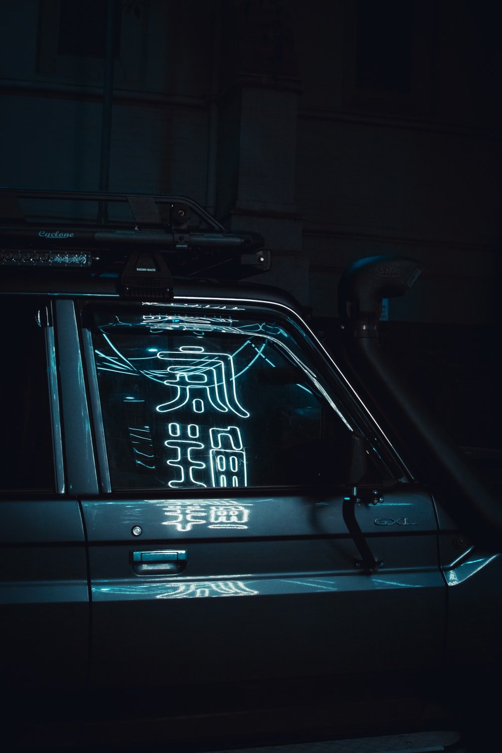parked car with kanji signage reflecting on it