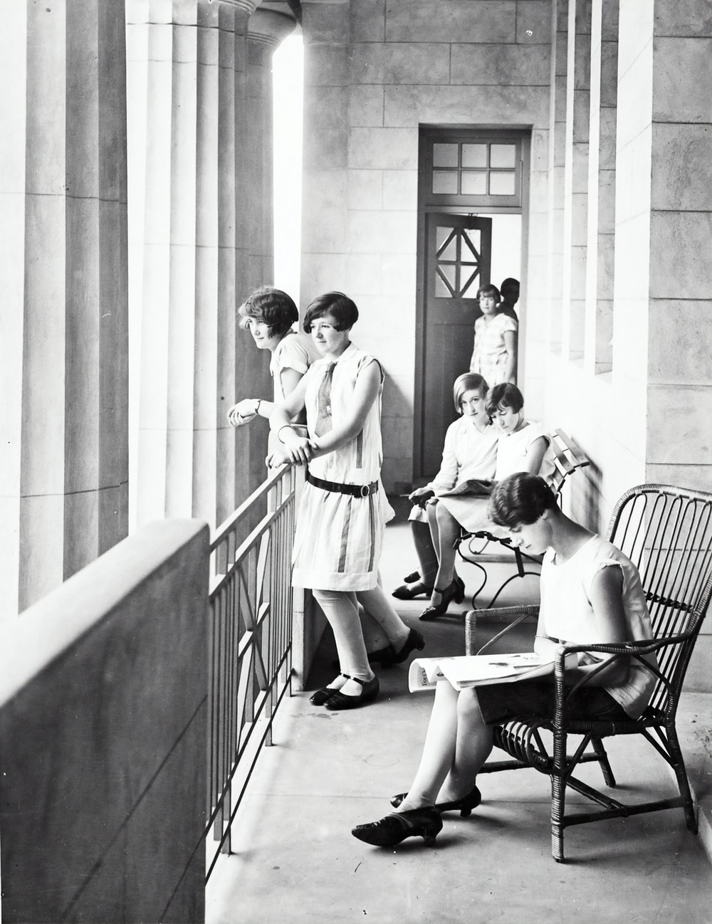 group of woman sitting and standing beside railing