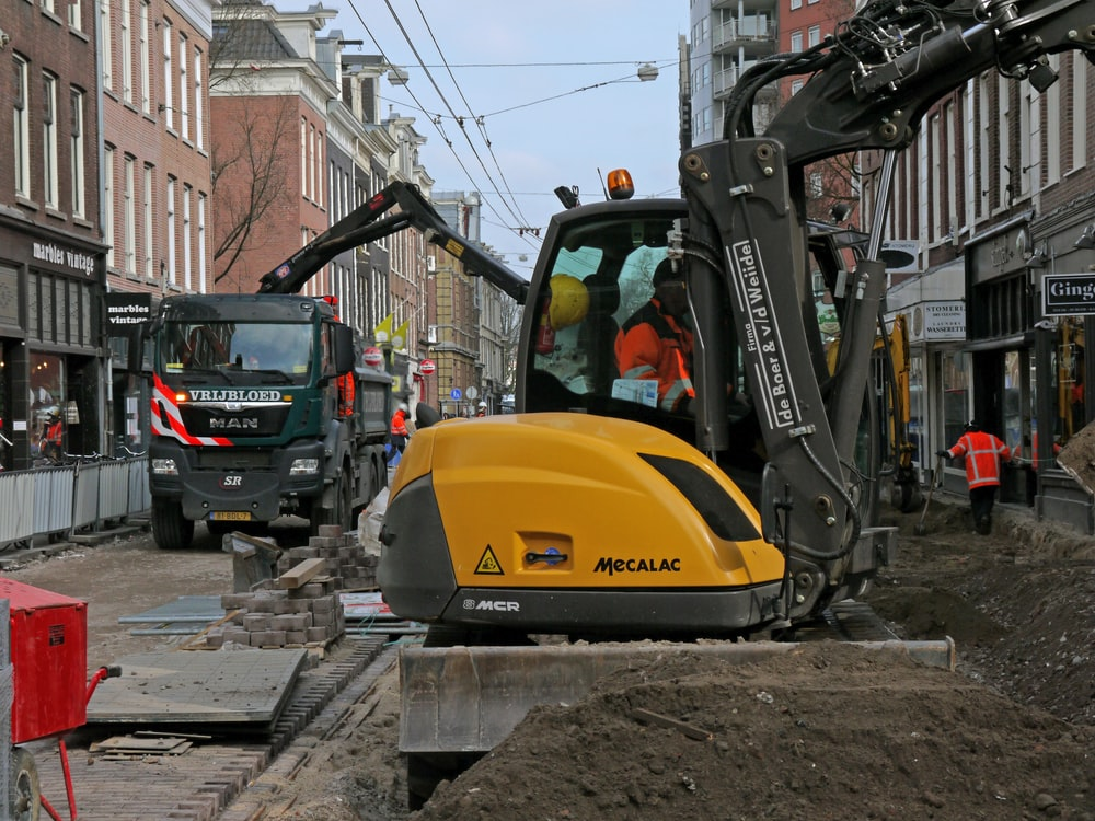 person using heavy equipment near vehicles, people, and buildings