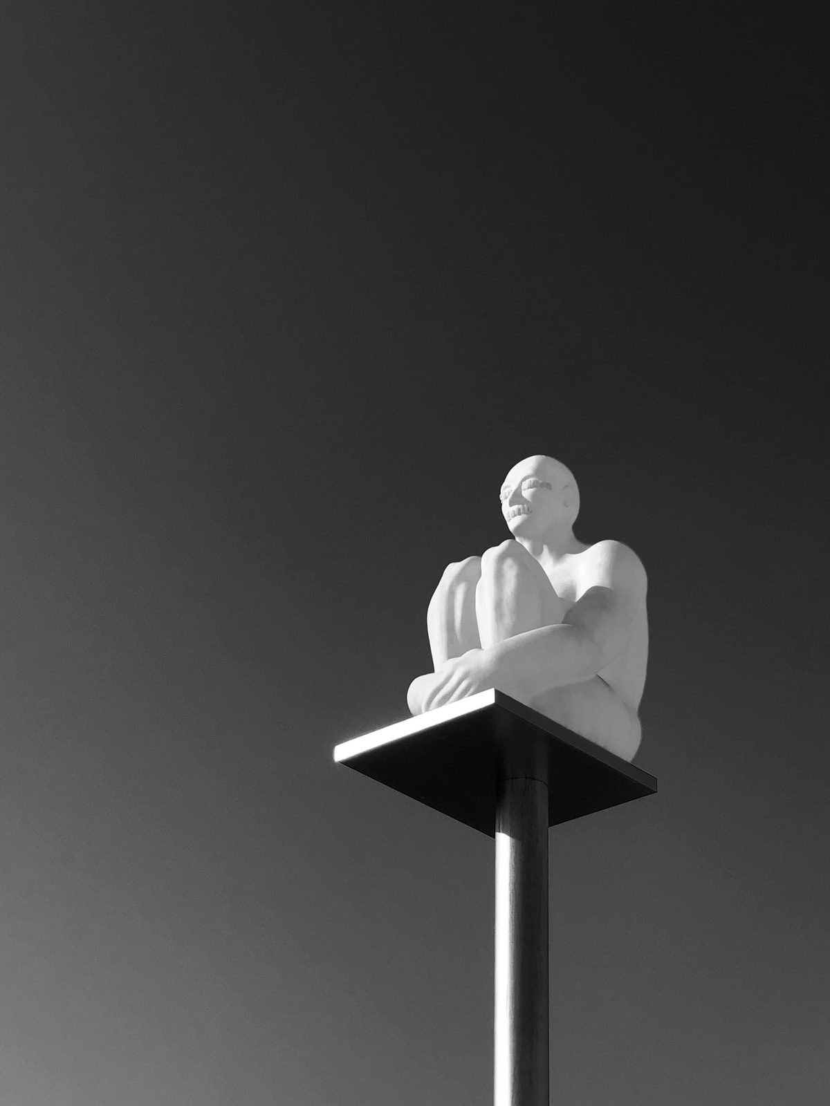 sitting man statue on post