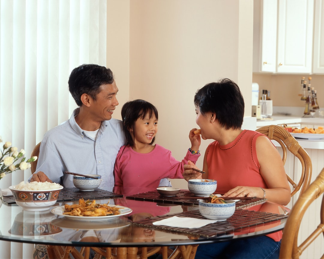 An Asian Family, An Adult Male and Female Are Seated Around A Table Eating A Meal With A Young Female Standing In Between the Adults. Photographer Rhoda Baer  - unsplash