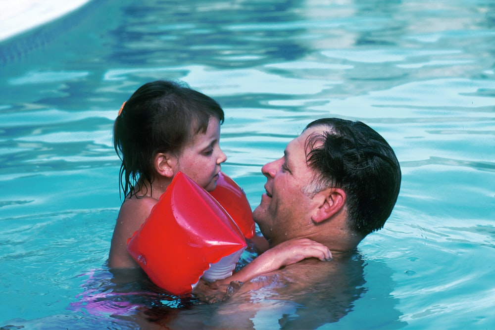 man with toddler girl in swimming pool