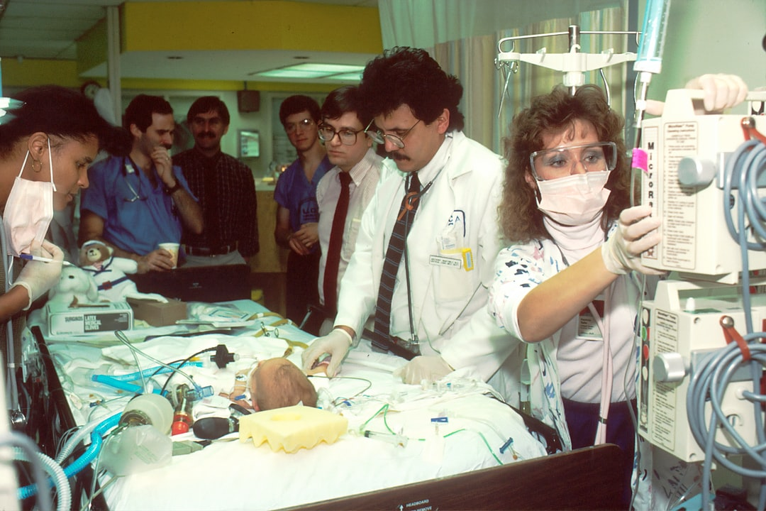 Doctors Examine Infant. A group of doctors examine an infant in the intensive care unit (ICU). Photographer Bill Branson