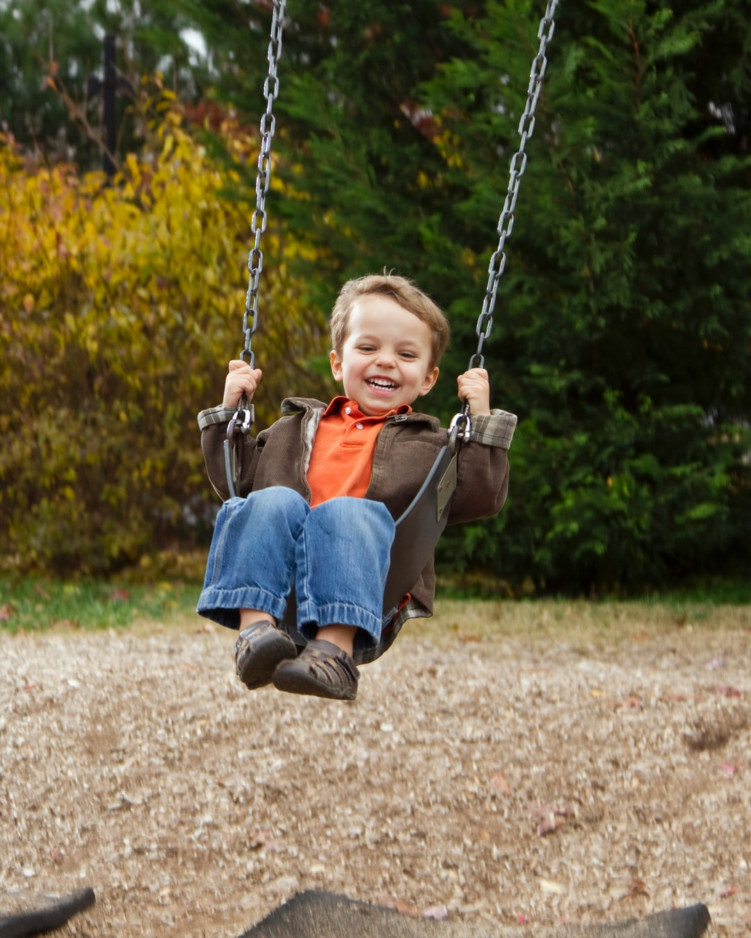 A Caucasian boy on a swing. Photographer Daniel Sone