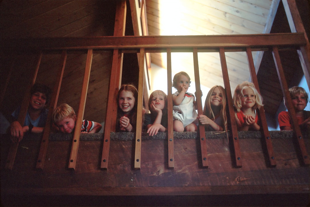 Children Sitting on a Staircase. Seven children peeking through a bannister railing on a staircase. They are members of a Mormon family who are presently being studied for their low cancer death rate. Pediatric, childhood, AYA. Photographer Linda Bartlett