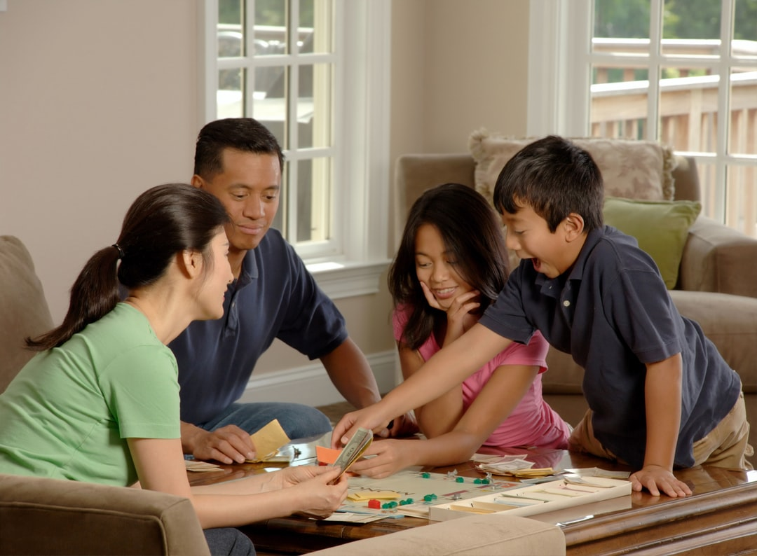 A family of four playing games in living room of a house