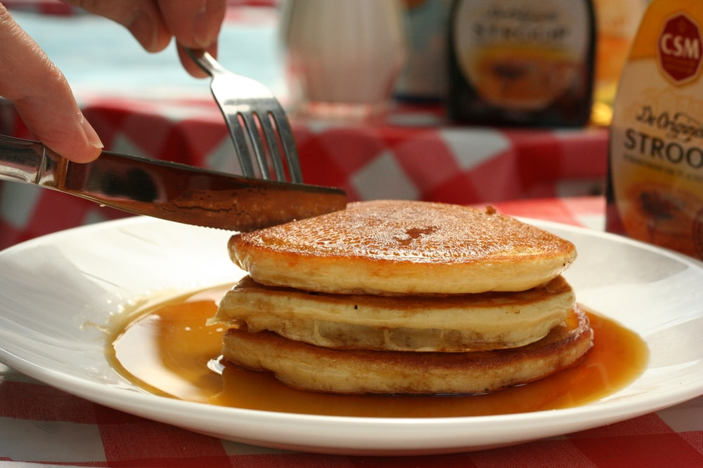 person slicing pancakes on plate