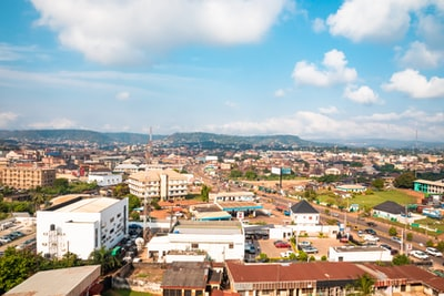 aerial photography of houses and buildings on green field viewing mountain under white and blue sky nigeria teams background