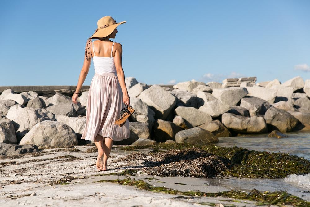 woman wearing brown sun hat walking on the seashore