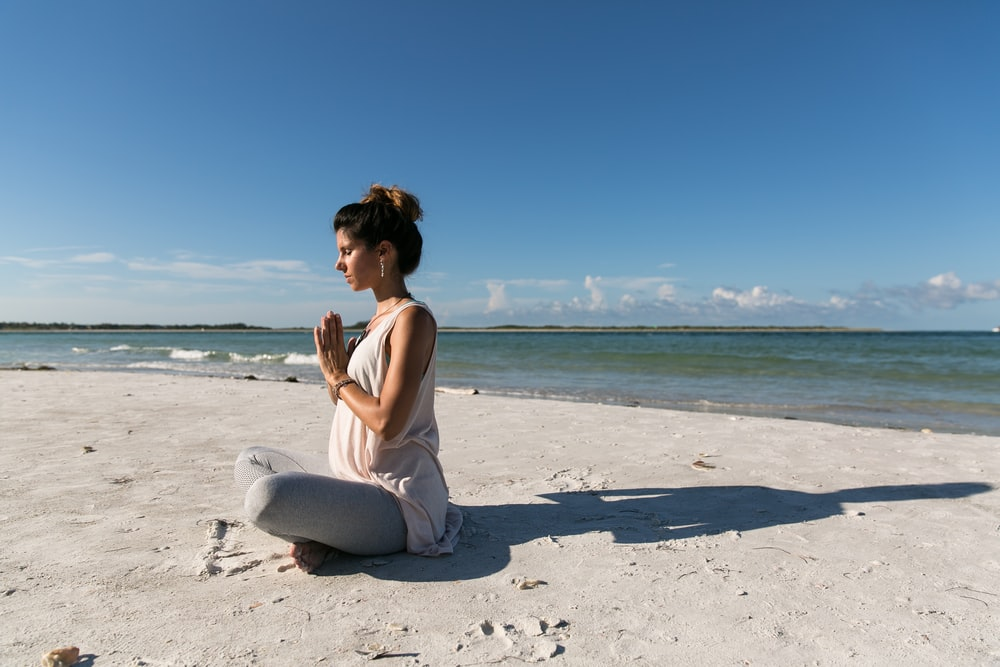 woman praying and sitting on sand seashore during day