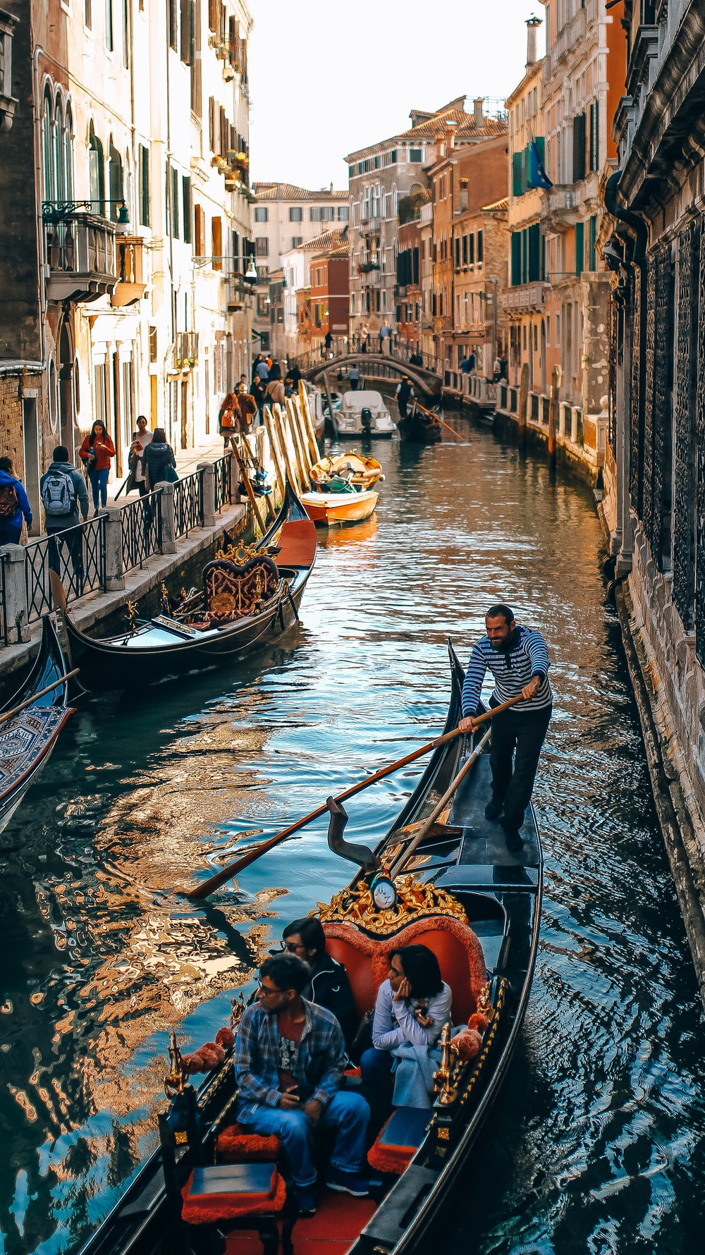 people in boat on Venice Canal during daytime
