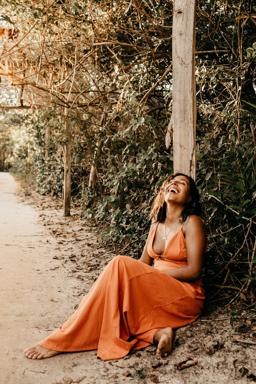 barefooted woman wearing orange spaghetti strap dress laughing while sitting on pathway surrounded with green trees