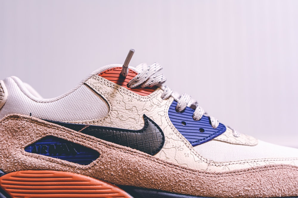unpaired white and brown Nike running shoe