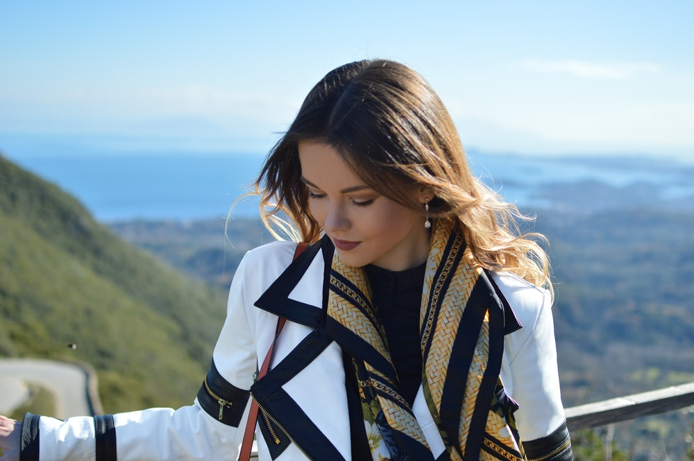 woman wearing white and black coat standing near railings while looking down viewing body of water and mountain under blue and white sky