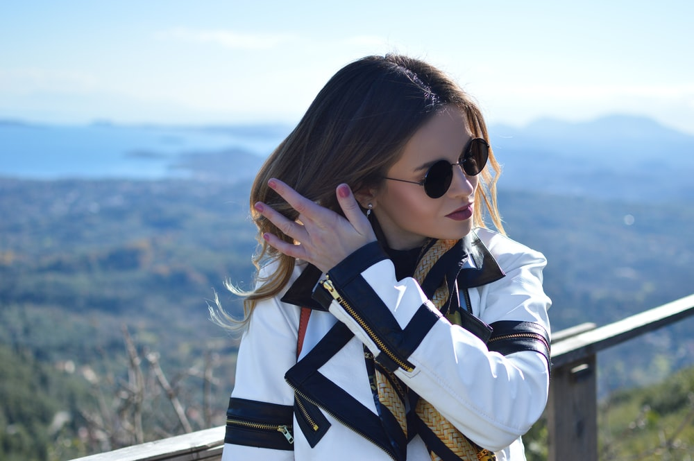 woman wearing white and black coat and sunglasses standing while fixing her hair viewing mountain under blue and white sky