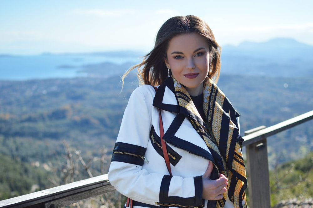 smiling woman wearing white and black coat standing near gray wooden railings viewing body of water and mountain under white and blue sky