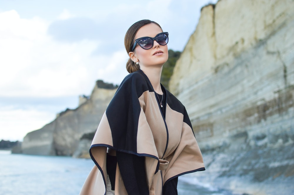 woman wearing black and brown dress and sunglasses standing near body of water under white and blue sky