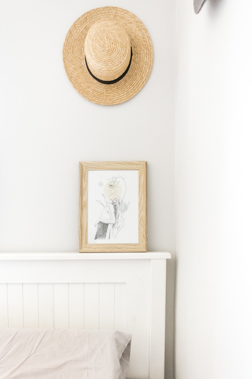 beige sun hat near abstract painting with brown frame beside wall