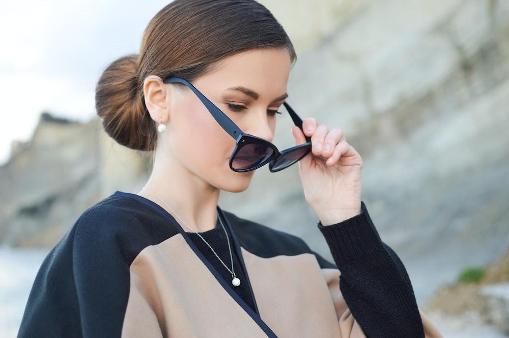 woman holding her black sunglasses