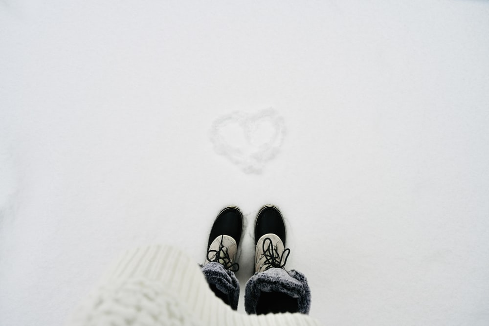 person wearing black-and-white shoes standing on snowy field with heart drawing