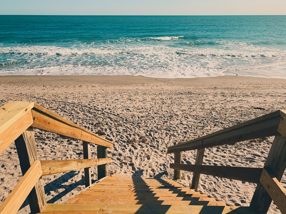 brown wooden stairs on sand seashore during day