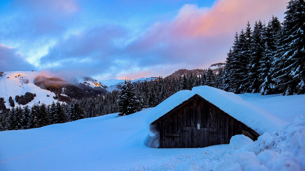 gray wooden houses covered with snow viewing mountain under blue and white sky