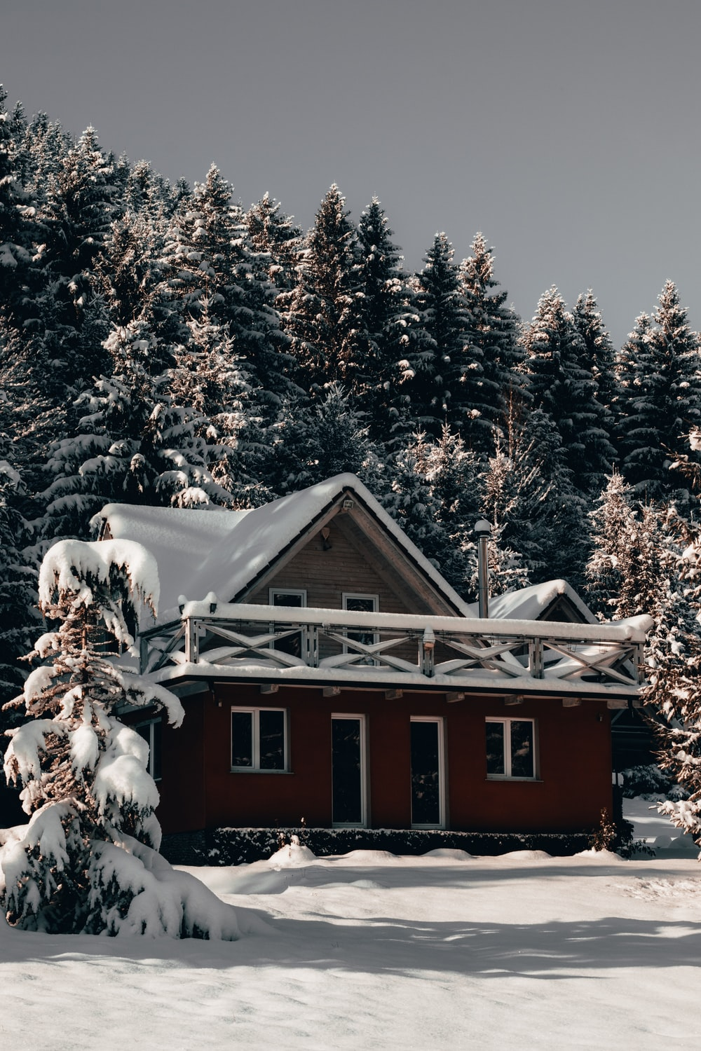 snow covered red house near trees during day