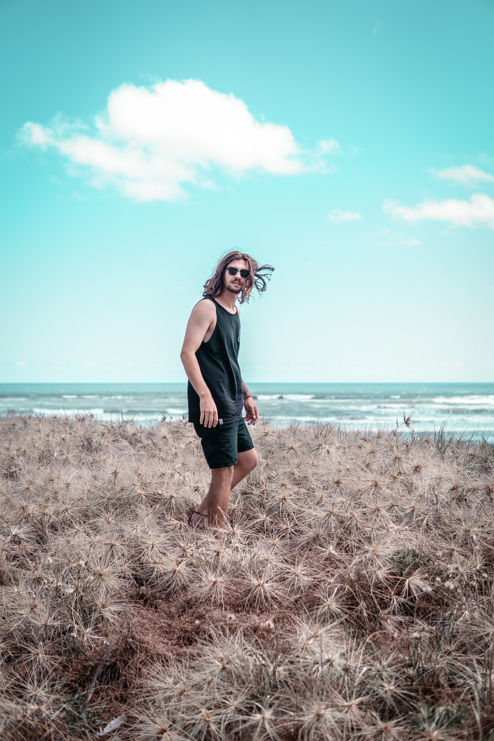 man in black tank top and black shorts standing outdoors
