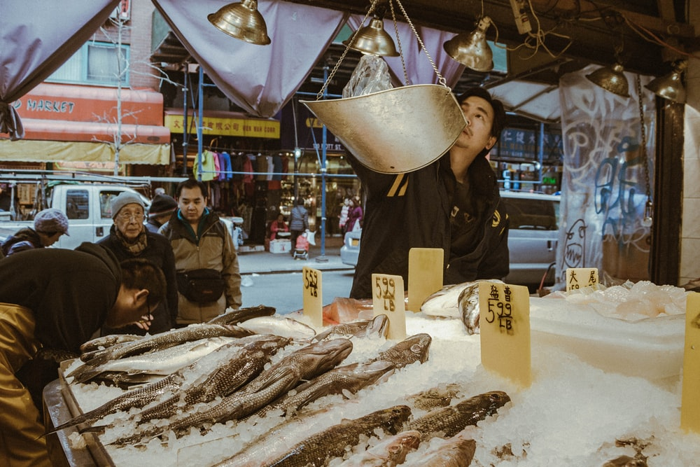 men standing beside fish stand