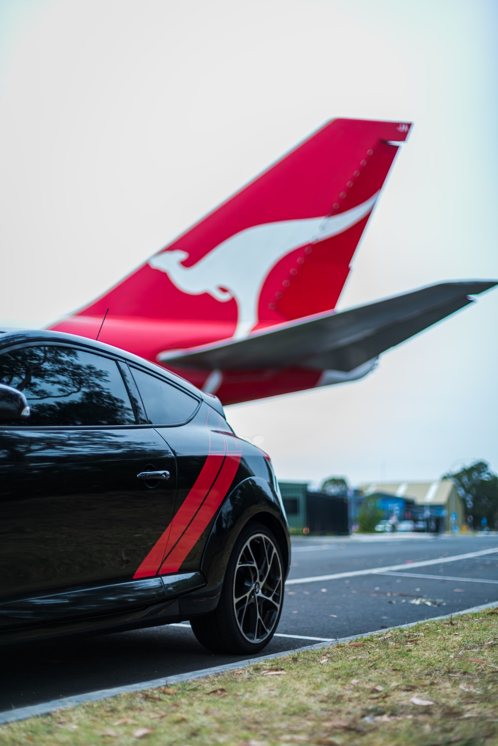 red and white airplane behind a black hatchback