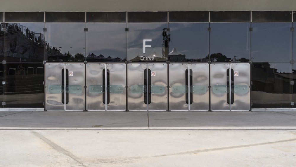 landscape photography of silver trash bins outside a building