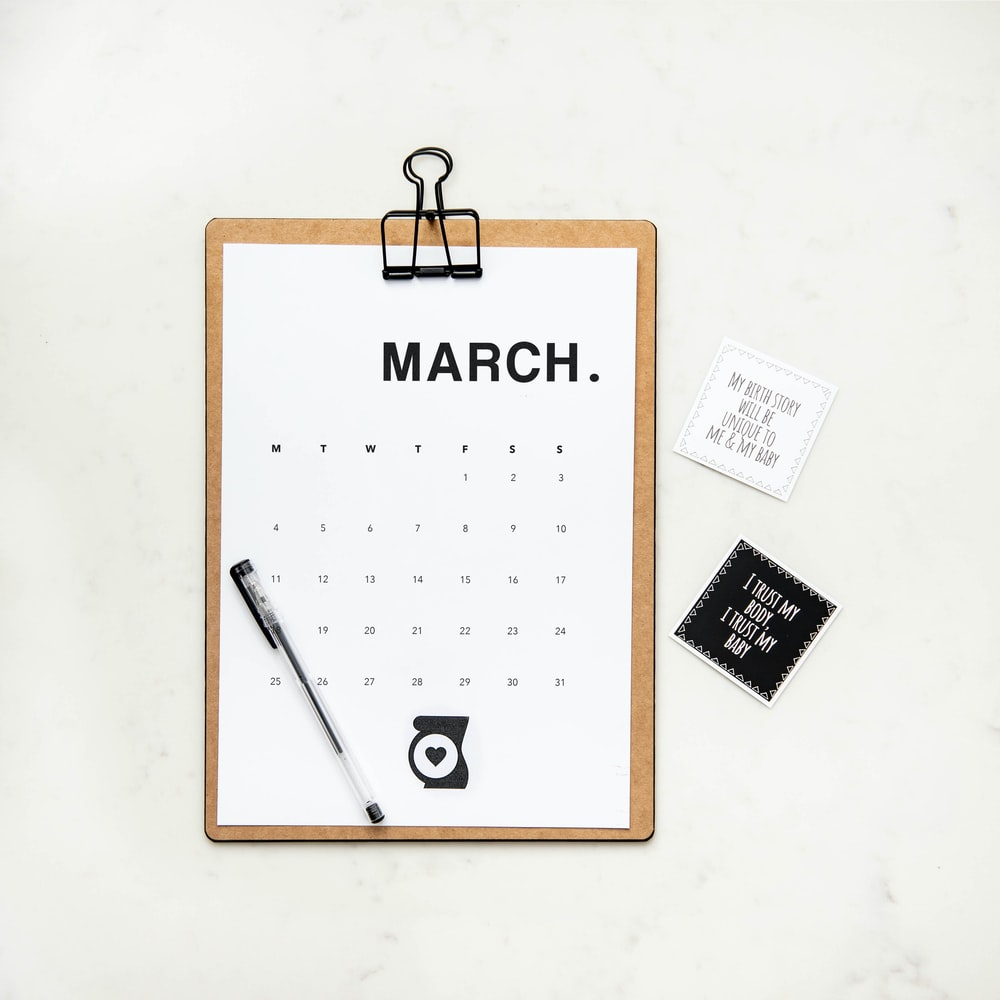 minimalist photography of a calendar with writing pen