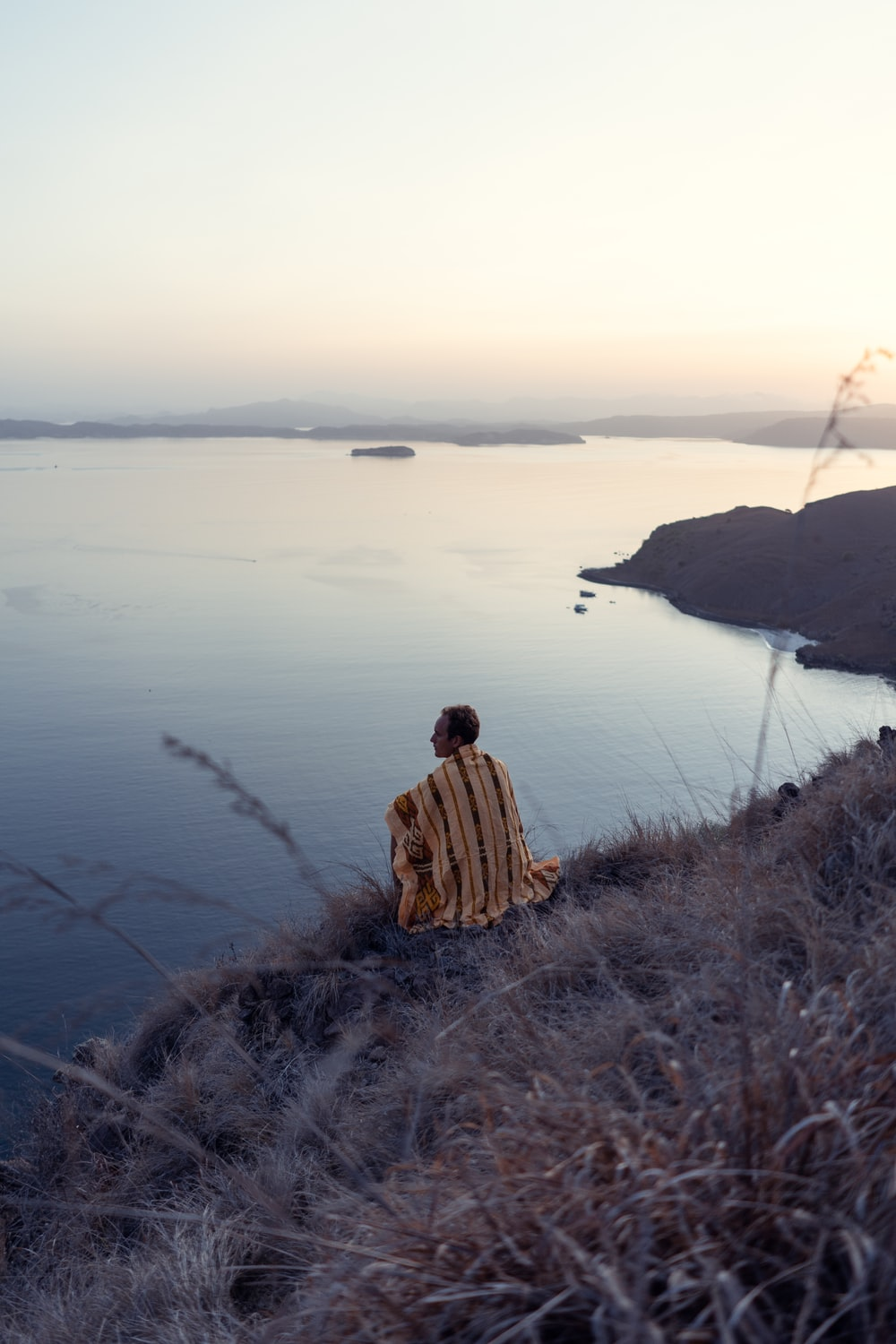 man sitting on cliff near body of water