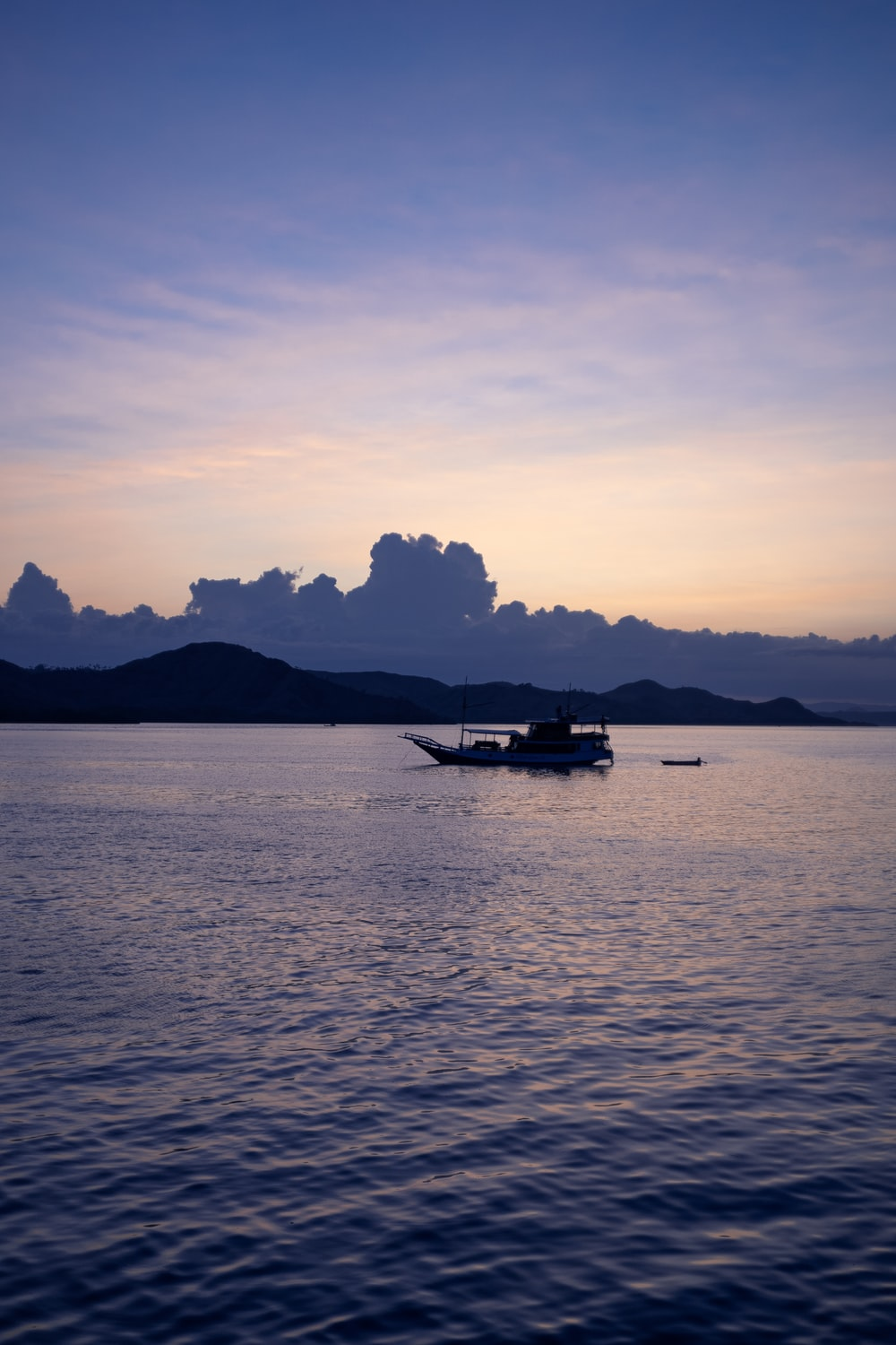 silhouette photography of a boat floating in the sea under a calm blue sky