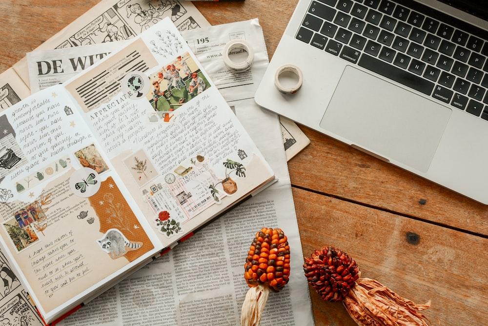MacBook Pro beside opened magazine