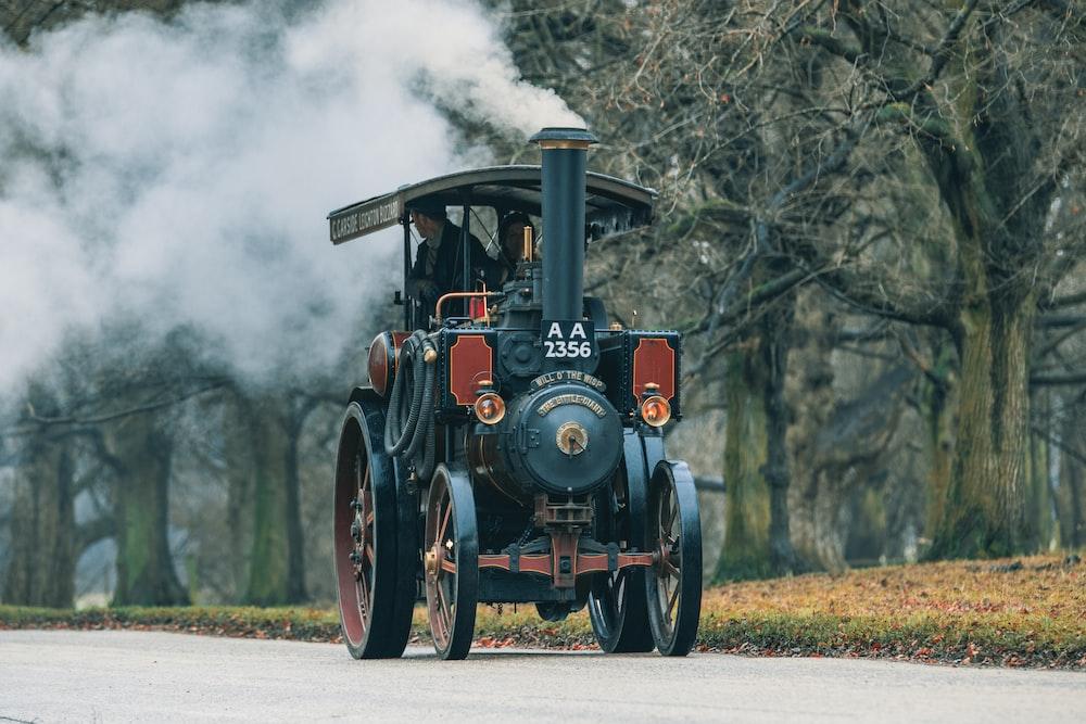 classic black and brown vehicle emitting smoke