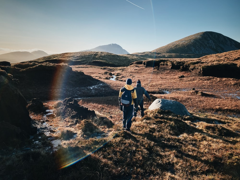 man and woman hiking on field