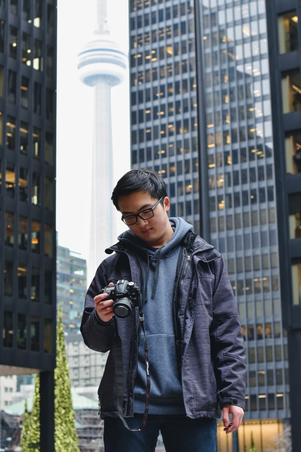 man in gray hoodie holding black DSLR camera outdoors