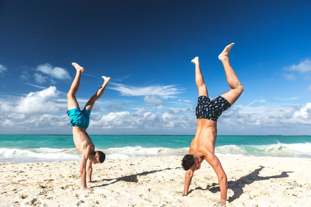 two people hand standing on sand