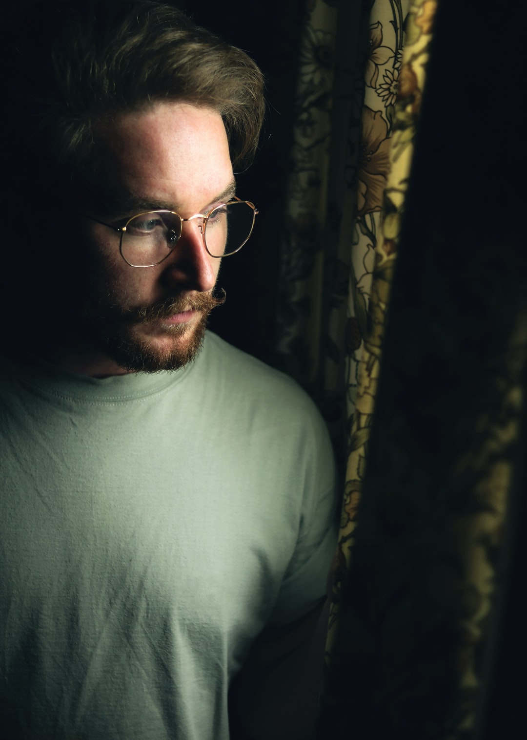 Man hiding behind curtain looking through the window with light coming through. vintage tones with retro moustache and wire frame glasses